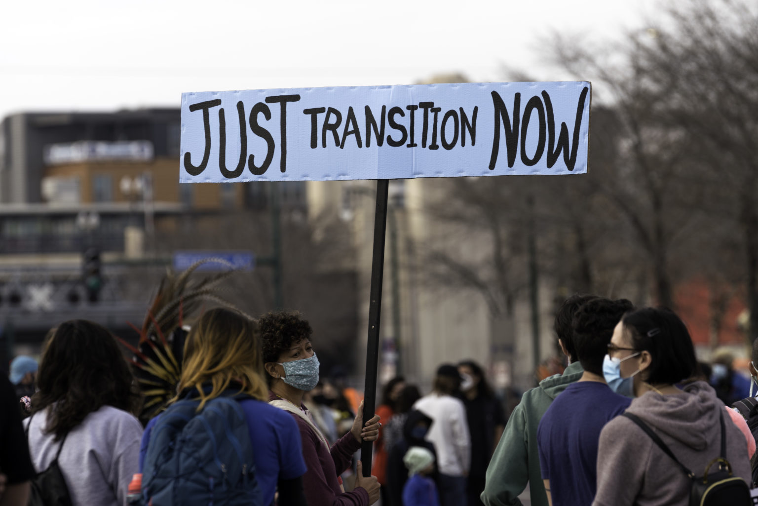 A_woman_holds_a_Just_Transition_Now_sign_at_a_rally_in_Minneapolis,_Minnesota_(50577736571)